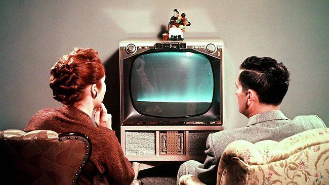 Parejita embobada viendo la tele a mediados de los años 50 (apróximadamente en el año 43 ABE -antes de Belén Esteban). La figurita encima del electrodoméstico ya se había impuesto entonces, aunque la ausencia de un paño de encaje debajo denote su origen anglosajón.