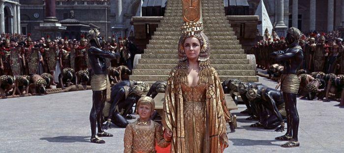 """""""Cleopatra"""" (Joseph Mankiewicz, 1963), también rodada en Todd-AO, hizo quebrar al estudio que la produjo a pesar de proporcionar unos más que respetables beneficios en taquilla. El motivo de que su presupuesto se inflara hasta 16 veces con respecto al original nada tuvo que ver con los costes del negativo, sino con un cúmulo de despropósitos, corrupción y decisiones estúpidas que no pudo esquivar ni siquiera el grandísimo Joseph Mankiewicz, coguionista y director que probablemente se acortó la vida 20 años intentando contener los excesos más bien mundanos de tanto ejecutivo imbécil."""